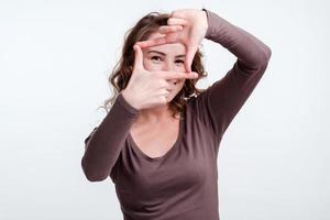 Mädchen machte einen rechteckigen Rahmen aus Fingern gegenüber ihren Augen foto