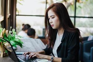 Asiatische Geschäftsfrauen, die Notebook zum Arbeiten verwenden foto
