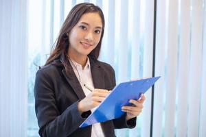 Asiatische Geschäftsfrauen, die glücklich lächeln, um zu arbeiten und Dokumente zu überprüfen foto