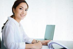 Asiatische Geschäftsfrauen, die Notebook verwenden und glücklich für die Arbeit lächeln foto