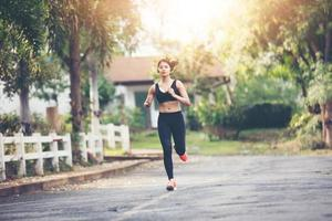 laufende Frau. Läuferin Joggen im Freien auf der Straße. Junge gemischte Rennen Mädchen Joggen foto