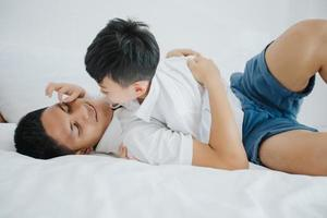 glückliche asiatische familie mit sohn zu hause im schlafzimmer, der spielt und lacht foto
