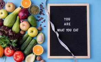 frisches Gemüse und Obst für eine gesunde Ernährung, Maßband und schwarzes Buchstabenbrett mit Wörtern, die Sie essen, Draufsicht flach mit Kopierraum foto