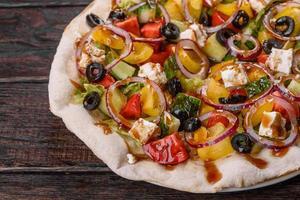 leckerer frischer griechischer Salat auf einem Fladenbrot zubereitet für einen festlichen Tisch foto