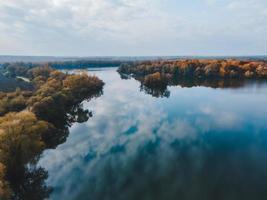 Luftaufnahme des herbstlichen Waldes mit Seehimmel, der sich im Wasser spiegelt foto
