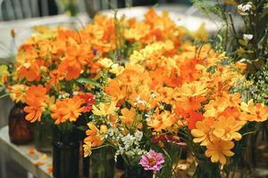 schöne Blumen in einer braunen Glasflasche, die morgens auf einem Tisch im Garten steht foto