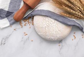 frischer hausgemachter Hefeteig ruht auf Marmortisch mit Weizenähren und Nudelholz. foto