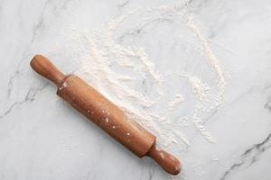 verstreutes Weizenmehl und Nudelholz auf weißem Marmorhintergrund flach. foto