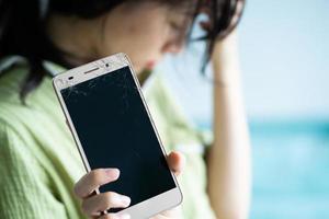 Asiatin ist traurig, weil ihr Handy kaputt ist foto