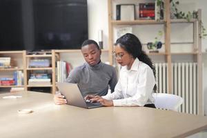junges schwarzes Paar, das in einem Büro arbeitet foto