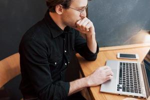 Kreativer Mann-Designer, der an seinem Laptop arbeitet, während er auf Bestellungen in seinem Lieblingscafé im Haus wartet, männlicher Student, der beim morgendlichen Frühstück im modernen Café-Interieur am Net-Book arbeitet foto