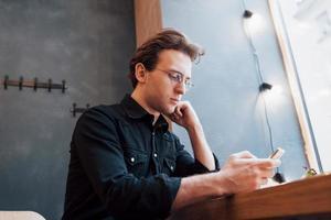 weicher Fokus. Mann, der das Telefon hält und verwendet. Beim Sitzen und Entspannen auf dem Sofa im modernen Haus. Konzept für junge Leute, die mit Mobilgeräten arbeiten foto