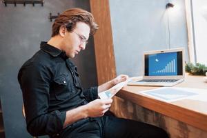 Geschäftsmann mit Laptop mit Tablet und Stift auf Holztisch im Café mit einer Tasse Kaffee. ein Unternehmer, der als Freiberufler sein Unternehmen aus der Ferne leitet. foto