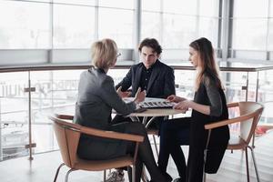 Teamjob erfolgreich. Foto junge Geschäftsleute, die mit einem neuen Startup-Projekt im Büro arbeiten. analysieren Dokument, Pläne. generisches Design-Notizbuch auf Holztisch, Papieren, Dokumenten