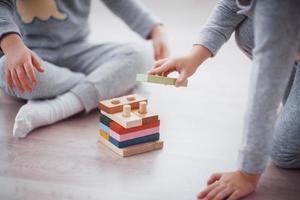 Kinder spielen mit einem Spielzeugdesigner auf dem Boden des Kinderzimmers. zwei Kinder spielen mit bunten Blöcken. Lernspiele im Kindergarten foto