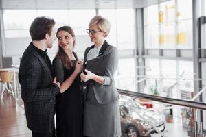junges Profiteam. Gruppe junger moderner Menschen in eleganter Freizeitkleidung, die ein Brainstorming-Meeting haben, während sie hinter der Glaswand im Kreativbüro stehen foto