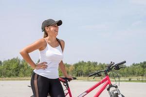 sorglose Frau, die in einem Park Fahrrad fährt und lacht foto
