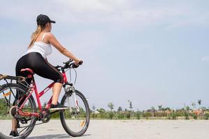 Rückansicht einer Frau, die in einem Park Fahrrad fährt foto