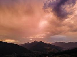 bewölkter Sonnenuntergang über Bergen foto