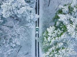 Blick auf das weiße Auto von oben im gefrorenen Winterwald foto