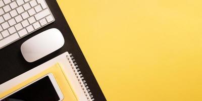 Flacher Desktop mit Tastatur, Telefon, Notizblock mit Kopienraum auf farbigem Hintergrund im Bannerformat foto