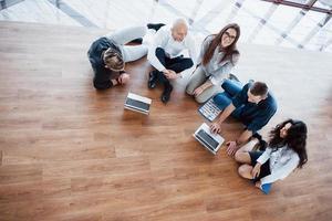 junge kreative leute im modernen büro. Gruppe junger Geschäftsleute arbeitet mit Laptop zusammen. Freiberufler sitzen auf dem Boden. Zusammenarbeit Unternehmenserfolg. Teamwork-Konzept foto