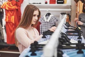 Verkauf, Mode, Konsum und Menschenkonzept - glückliche junge Frau mit Einkaufstaschen, die Kleidung im Einkaufszentrum oder Bekleidungsgeschäft auswählen foto