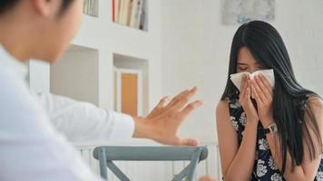 eine junge Frau, die niest, während sie mit einem männlichen Partner arbeitet. Er hatte Angst vor Covid-19. foto