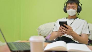 männlicher Student mit Maske, der ein Smartphone verwendet, um mit einem Freund zu sprechen, um sich auf die Prüfung vorzubereiten, die er zu Hause studiert hat, um Covid-19 zu schützen. foto