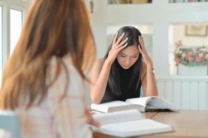 zwei asiatische studentinnen lesen fleißig, um sich auf das studium vorzubereiten. foto