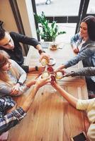 Ausblick von Oben. Hände von Menschen mit Gläsern Whisky oder Wein, die zu Ehren der Hochzeit oder einer anderen Feier feiern und anstoßen foto
