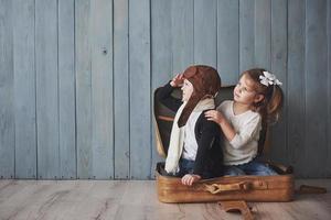 glückliches Kind im Pilotenhut und kleines Mädchen, das mit altem Koffer spielt. Kindheit. Fantasie, Fantasie. Reisekonzept foto