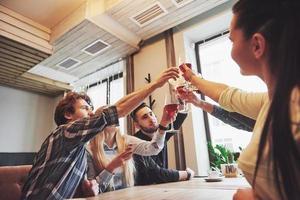 Hände von Menschen mit Gläsern Whisky oder Wein, die zu Ehren der Hochzeit oder einer anderen Feier feiern und anstoßen foto