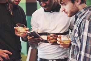 vielversprechende junge multiethnische Menschen feiern und trinken Whisky-Toast, schauen Sie sich Gadget an foto