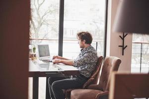 Junger gutaussehender Mann, der mit einer Tasse Kaffee im Büro sitzt und an einem Projekt arbeitet, das mit modernen Cyber-Technologien verbunden ist. Geschäftsmann mit Notebook, der versucht, die Frist im Bereich des digitalen Marketings einzuhalten? foto
