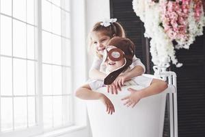 Porträt eines Mädchens und eines Jungen in Pilotenmütze, die im Badezimmer bei Piloten oder Matrosen spielen. das Konzept des Reisens, der Kindheit und der Verwirklichung von Träumen foto