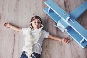 Kind gibt vor, Pilot zu sein. Kind hat Spaß zu Hause. Vintage Pilot und Reisekonzept. Porträt von oben foto