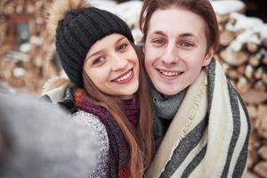 Weihnachten glückliches Paar in der Liebe umarmt im verschneiten kalten Winterwald, Kopienraum, Neujahrsfeier, Urlaub und Urlaub, Reisen, Liebe und Beziehungen foto