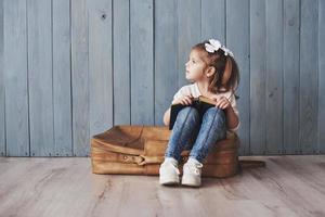 bereit für große Reisen. glückliches kleines Mädchen, das ein interessantes Buch liest, das eine große Aktentasche trägt und lächelt. Reise-, Freiheits- und Vorstellungskonzept foto
