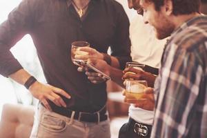 Whiskey. Gruppe von Freunden mit Gläsern Whisky. Konzeptparty, Junggesellenabschied Friseursalon. foto