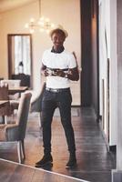 modischer afroamerikanischer Mann mit Hut mit einem Glas Whisky foto
