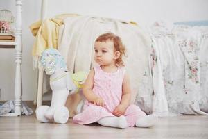 schönes kleines Mädchen, das Spielzeug spielt. blauäugige Blondine. weißer Stuhl. Kinderzimmer. glückliches kleines Mädchenporträt. Kindheit Konzept foto