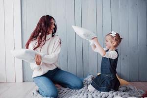 glückliche familie die mutter und ihr kind kämpfen gegen kissen. fröhliche familienspiele foto