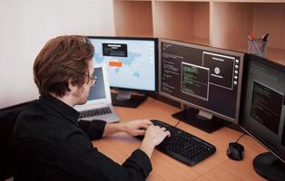 Männlicher Programmierer, der an einem Desktop-Computer mit vielen Monitoren im Büro in einer Softwareentwicklungsfirma arbeitet. Website-Design-Programmierung und Codierungstechnologien foto