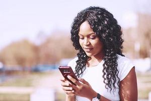 Nahaufnahme Porträt einer attraktiven Frau mit Handy auf der Stadtstraße foto