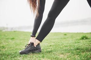 junge Fitnessfrau, die Beine ausdehnt, bevor sie im Park läuft foto