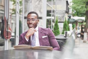 Ein schöner afroamerikanischer Geschäftsmann liest eine Speisekarte in einem Café? foto