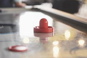 Airhockeytisch mit Fensterbeleuchtung und rotem Spielzeughockeyschläger foto