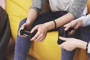 Zwillingsschwestern spielen auf der Konsole. Mädchen halten Joysticks in den Händen und haben Spaß foto