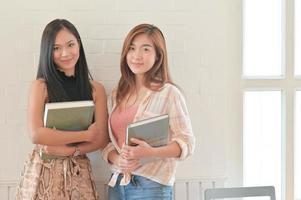 ein Porträt von zwei asiatischen Studentinnen, die ein Buch halten. sie bereiten sich auf ein universitätsstudium vor. foto